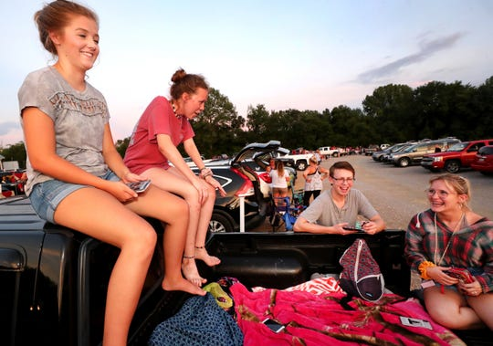 "From left, Emma Shelton, 17, Jazzy Sartin, 16, Nolan Hills, 17, and Anna Kneip, 17, hang out in the back of a pickup truck before the start of ""The Lion King"" at the Moonlite Drive-in."
