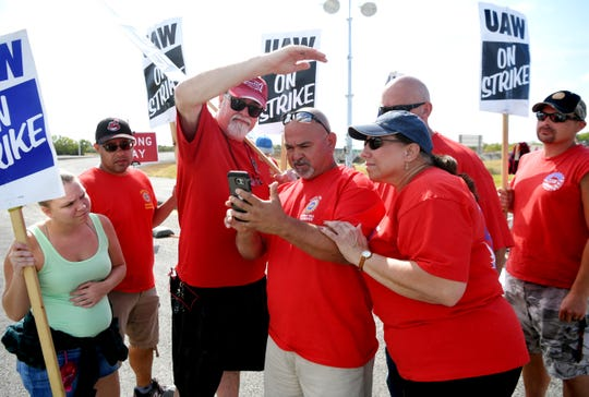 Strikers gather around as Richard Reyse reads an update on the status of negotiations on the strike against General Motors at the north gate of the GM Spring Hill Plant Wednesday.