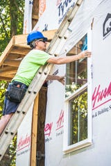 Crew leader Grayling Pruitt installs a window at Habitat for Humanity's Building on Faith Build Day in Fairview on Sept. 14, 2019.