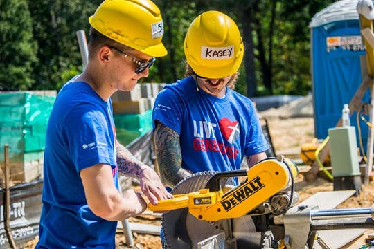 Volunteers cut siding for a home in Fairview during Habitat for Humanity's Building on Faith Build Day on Sept. 14, 2019.