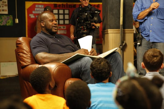 Retired basketball player Shaquille O'Neal reads to children.