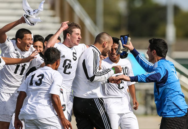 The Gulf Coast High boys soccer team celebrates with coach Alan Scott after winning the Class 4A state championship with a 2-0 win against Steinbrenner on Feb. 16, 2013 in Melbourne.