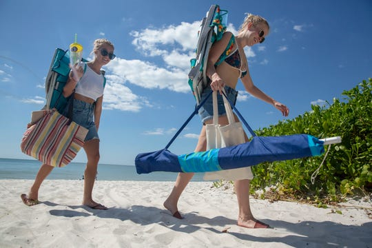 Virginia Lundstrom, right, and Olivia Tronnier, left, walk through the Horizon Way beach access on Wednesday, Sept. 25, 2019, in Naples. Collier County plans to use Horizon Way beach access to bring in sand to the southern portion of the beach renourishment while a conveyor system will be used at the pedestrian access to Seagate Beach to haul in sand at the northern section.