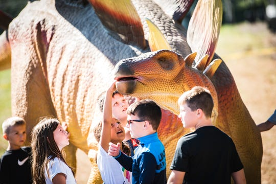 Students from Licking County schools react to a dinosaur at Legend Valley on Tuesday, Sept. 24, 2019 ahead of Lost Lands Music Festival.