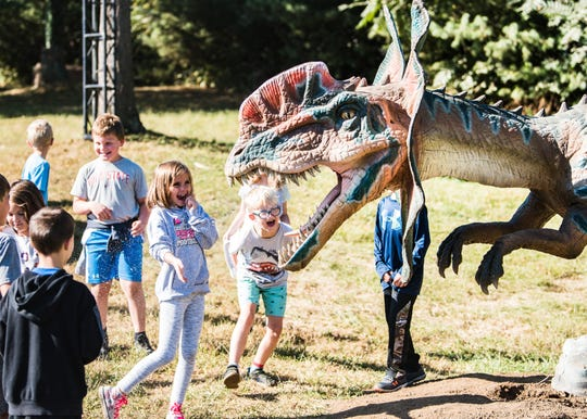 Students from Licking County schools react to an animatronic dinosaur at Legend Valley on Tuesday, Sept. 24, 2019 ahead of Lost Lands Music Festival.