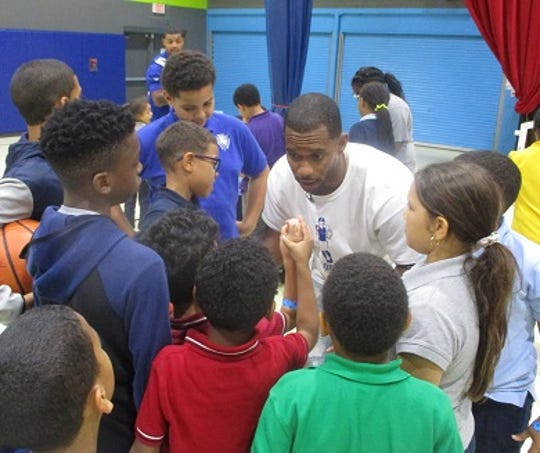 Victor Cruz huddles with children at the Boys and Girls Club of Paterson and Passaic.
