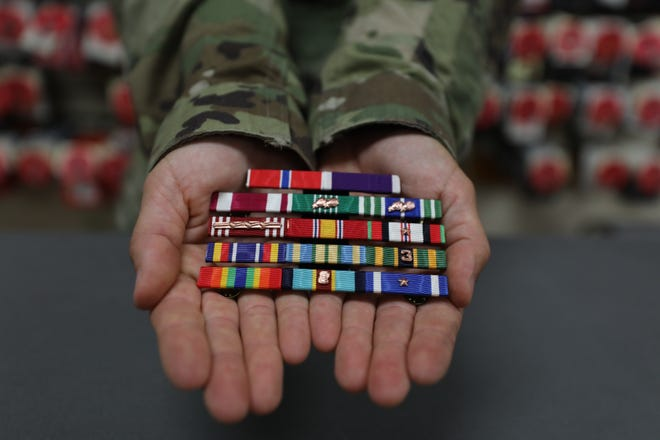 US Army First Sgt. Nicole McMinamin works in the room that stocks all the uniforms as well as decorations and insignias that will be used as part of the uniform to dress the deceased members of the military. The ribbons she holds are part of what she puts together for the fallen. It is part of the mortuary at Dover Air Force Base in Delaware where the remains of America's military who have fallen arrive and are prepared before being released to their families.