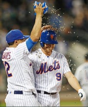 New York Mets' Juan Lagares (12) showers Brandon Nimmo with sunflower seeds after Nimmo drew a bases-loaded walk to drive in the winning run in the Mets' 5-4 victory over the Miami Marlins in 11 innings in a baseball game Tuesday, Sept. 24, 2019, in New York.