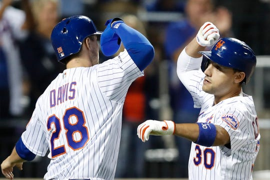 New York Mets' J.D. Davis (28) celebrates with Michael Conforto after scoring on Conforto's home run during the seventh inning of a game against the Miami Marlins on Tuesday, Sept. 24, 2019, in New York.