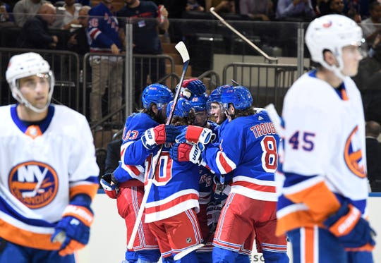 New York Rangers left wing Artemi Panarin (10) reacts with teammates after scoring a goal during the second period against the New York Islanders at Madison Square Garden.