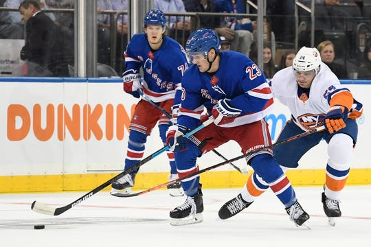 New York Rangers defenseman Adam Fox (23) skates with the puck against New York Islanders defenseman Scott Mayfield (24) during the first period at Madison Square Garden.