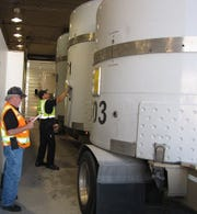 Fluor Idaho Transportation Certification Official Shawn Strozzi, left, double-checks the 500th shipment's manifest as Idaho State Trooper Peter Sibus conducts an inspection of the shipment.