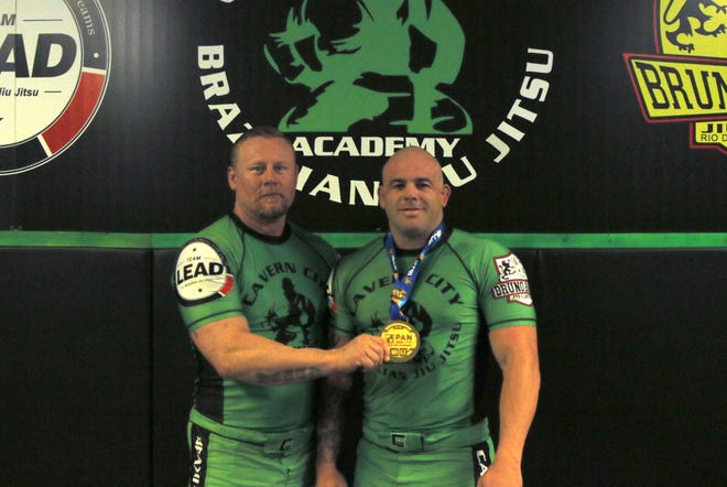 Cavern City BJJ owner Kevin Heath, left, displays Bo Bowen's medal Bowen won the Master's I Blue Belt Super Heavy division at the Pan Jiu-Jitsu No-Gi Championship in New York on Sept. 15. Bowen is currently ranked No. 5 in the International Brazillian Jiu-Jitsu Federation in the blue belt division.
