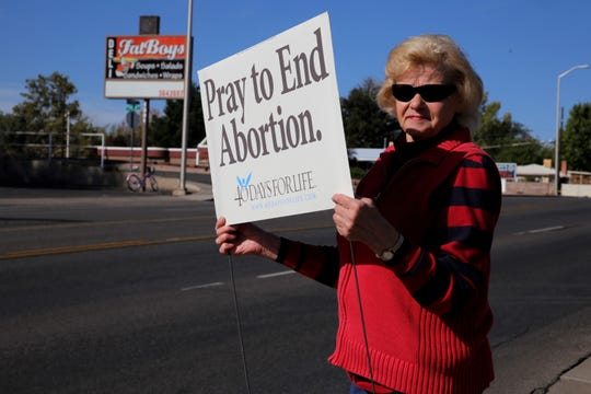 Patricia Wagner holds a sign, Wednesday, Sept. 25, 2019, during the first day of the 40 Days for Life protests in front of Planned Parenthood of Farmington.