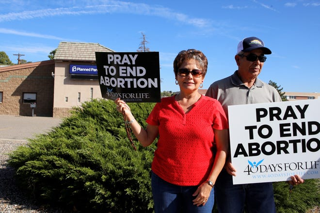 Roselie and Alfred Valdez hold signs protesting abortion, Wednesday, Sept. 25, 2019.