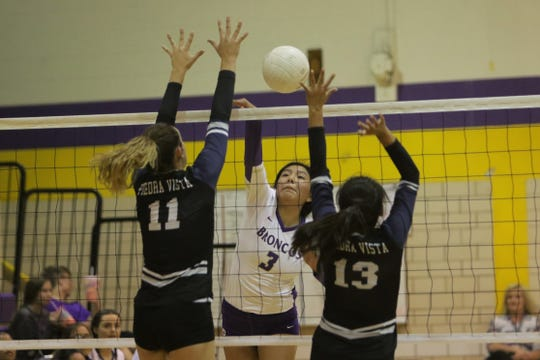 Kirtland Central's Gabrianna White-David hits the ball right between past Piedra Vista's Bailey Rasmussen (11) and Angelete Clyde (13)  during Tuesday's volleyball match at Karlin Gym in Kirtland.
