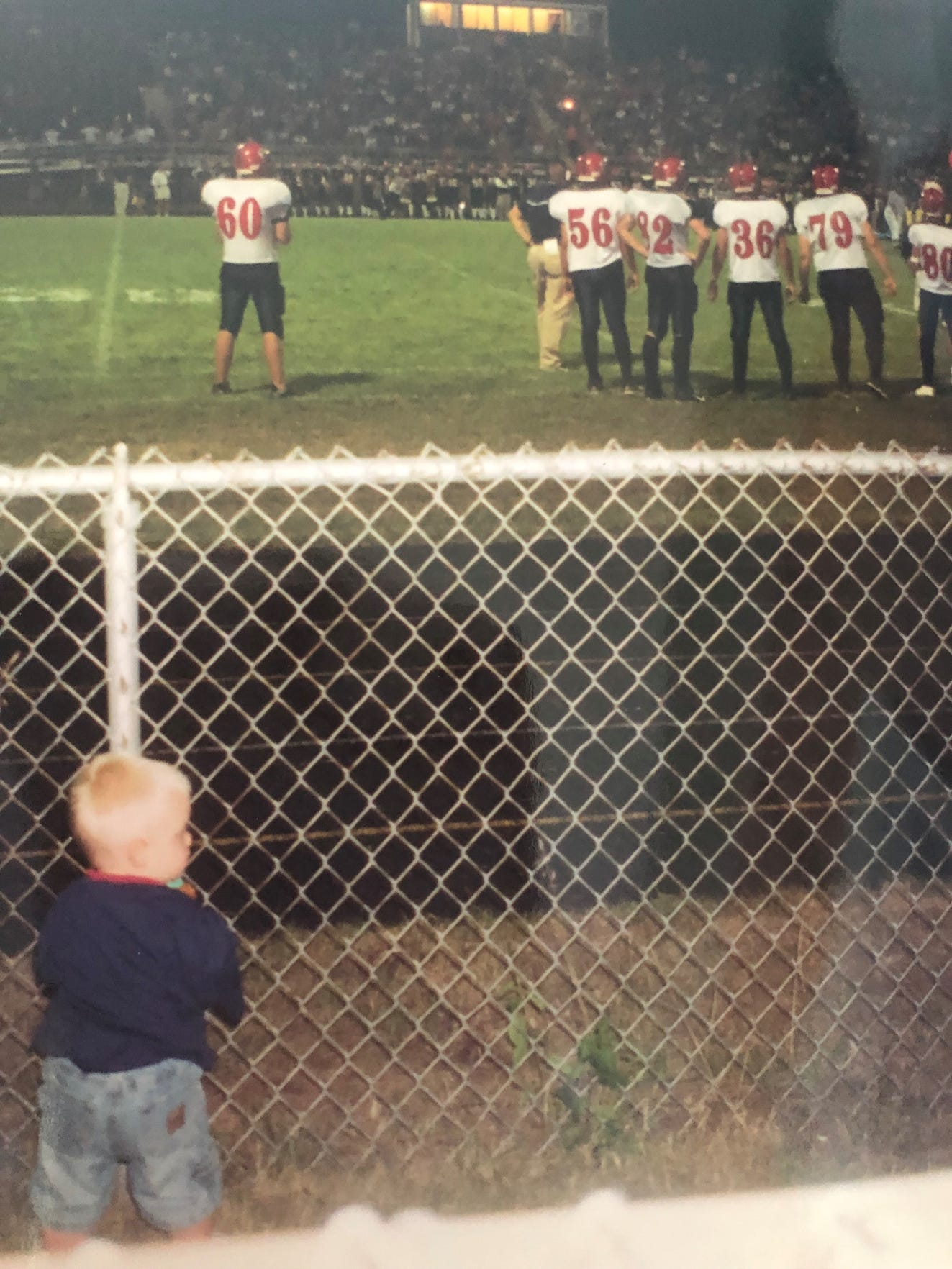 Jake Kelbert stands behind the fence, watching his father Chris Kelbert coach on the sideline.