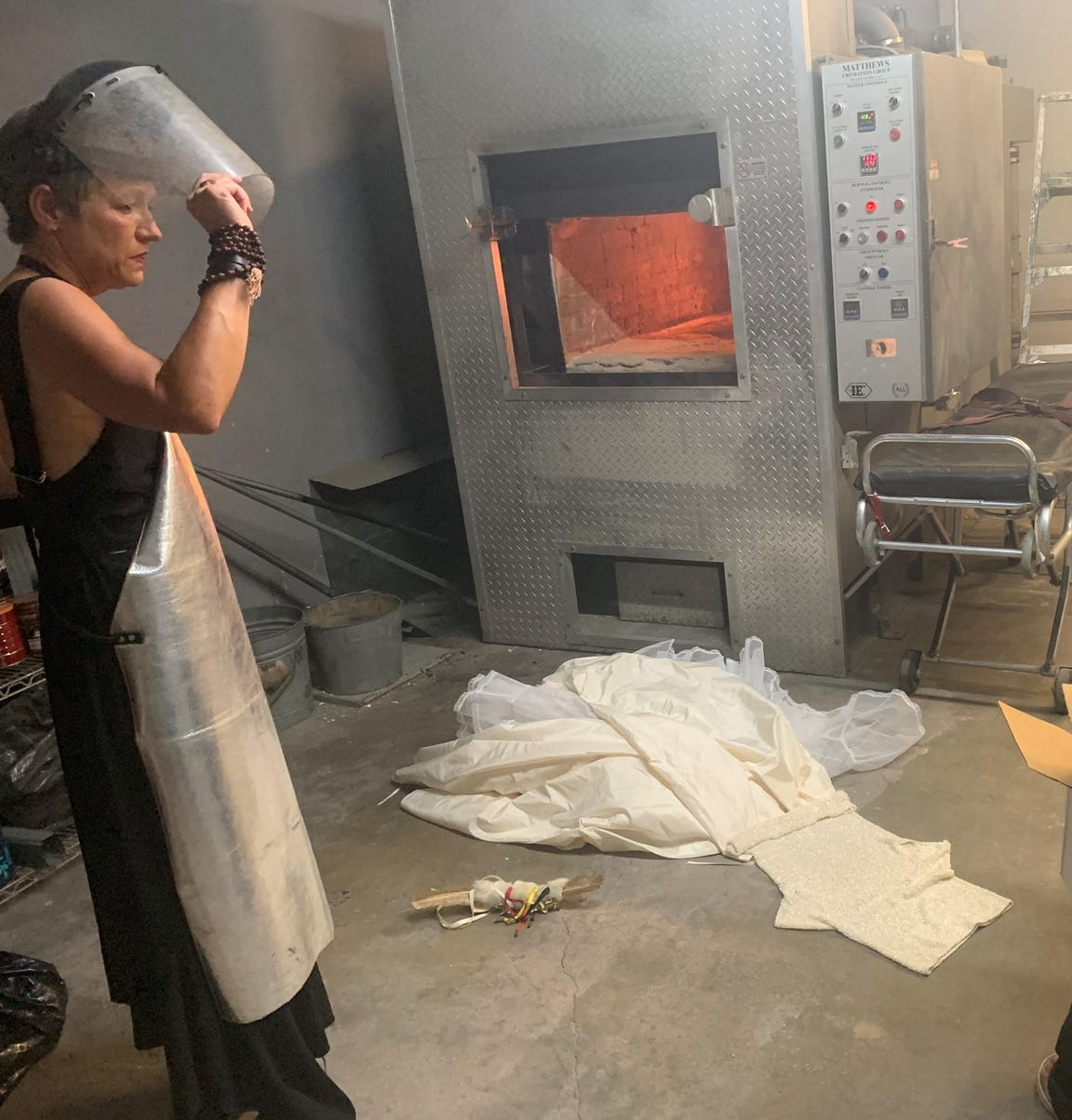 Marcel Sitcoske, in protective gear, about to toss her wedding dress into the flames in September, 2019.