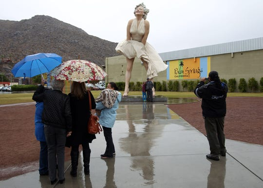 """Tourists snap photos at the """"Forever Marilyn"""" statue on Friday, Nov. 22, 2013, in Palm Springs."""