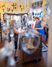 Owner Debbie Tracy, right, wraps up Susan Haines' purchase at Angel's Garden Unique Gifts on 12th Avenue in Pensacola on Wednesday, Sept. 25, 2019.  The Historic 12th Avenue Business Owners Association, that is starting up again after being dormant since the hurricanes Ivan and Dennis, is hoping to improve walkability and lighting along the corridor.