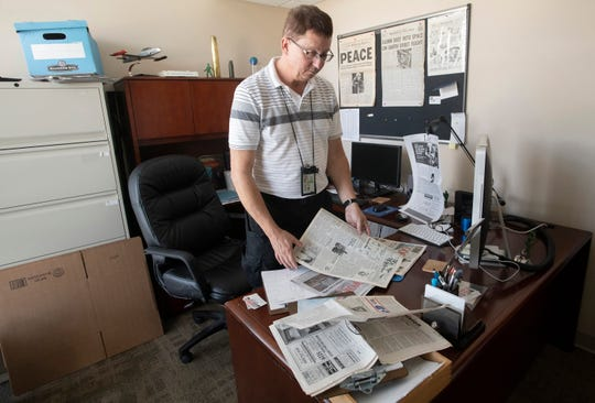Gosport Managing Editor Mike O'Connor looks over historical copies of the publication on Tuesday. The newspaper, which served Naval Air Station Pensacola, is ceasing publication after 98 years.