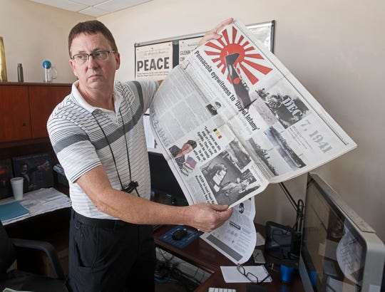 Gosport Managing Editor Mike O'Connor shows off one of his favorite stories. The newspaper, which served Naval Air Station Pensacola, is ceasing publication after 98 years.
