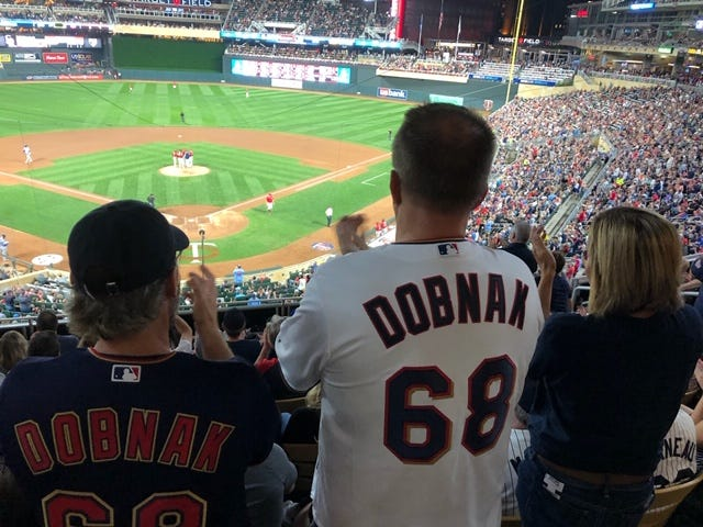 Chris Janes (middle) and Jason Hedgepeth, left, wear their Randy Dobnak jerseys while watching former Blue Wahoos pitcher make his first start, and get the win, last Friday for the Minnesota Twins.