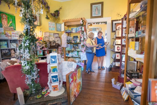 Owner Debbie Tracy, right, shows Jill Clark some books at Angel's Garden Unique Gifts on 12th Avenue in Pensacola on Wednesday, Sept. 25, 2019.  The Historic 12th Avenue Business Owners Association, that is starting up again after being dormant since the hurricanes Ivan and Dennis, is hoping to improve walkability and lighting along the corridor.