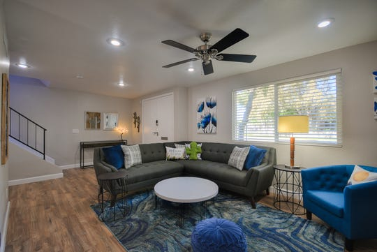 The remodeled living room features new floors, comfortable seating and an entryway that doesn't leave anyone scratching their head. Homeowner Stacy Karel's special touch: the handmade crocheted Saguaro throw pillow on the sofa.