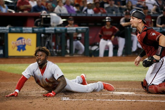 Former Springfield Cardinals Randy Arozarena, left, and Arizona Diamondbacks catcher Caleb Joseph, right, wait for the umpire to make a call at home plate during the fourth inning of a baseball game Wednesday, Sept. 25, 2019, in Phoenix. Arozarena was ruled safe at home for a run scored against the Diamondbacks.