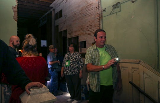 """Tim King, a tour guide, directs the crowd's attention towards writing on the wall inside a site featured in the """"History and Mystery Tour"""" paranormal tour in Dallas, Oregon, Sept. 24, 2019."""
