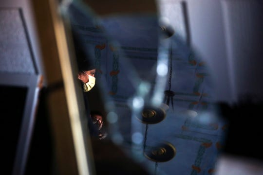 """Kristina Rasmussen, a tour guide, is reflected in a shattered mirror at one of the sites featured in  the """"History and Mystery Tour"""" paranormal tour in Dallas, Oregon, Sept. 24, 2019."""