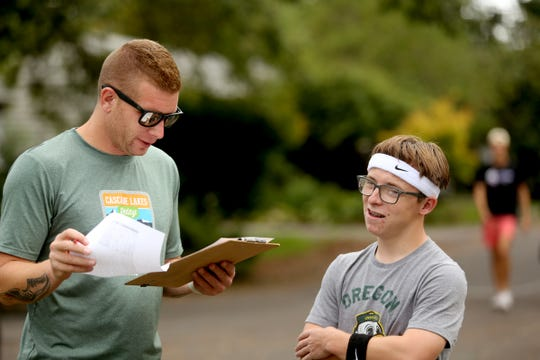Robert Salberg, a coach, talks with Jackson Campbell, a junior, during South Salem High School cross country practice at Bush's Pasture Park in Salem on Sep. 23, 2019. Jackson, who has a cognitive disability, completed his first cross country race after a teammate he didn't know well ran alongside him during a recent meet, encouraging him to finish.