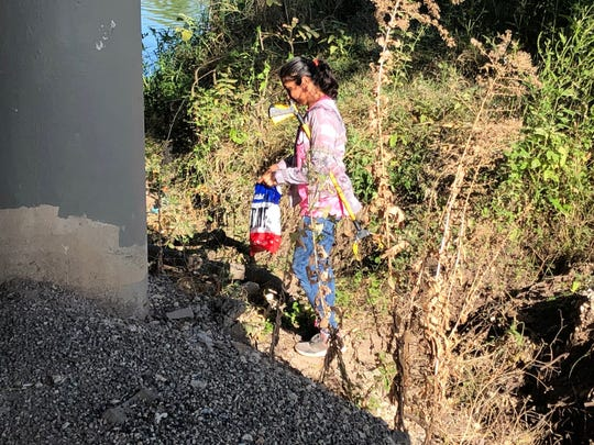 Carmen Torres cleans up litter under San Angelo bridges.