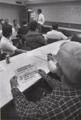 Municipal Court Judge Allen Gilbert shows a group of merchants and concerned citizens a photocopy of a no trespassing sign and discusses its wording during a meeting at El Patio Motor Inn in October of 1989.