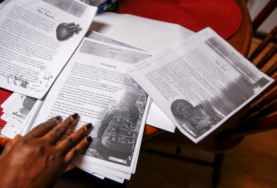 Francia Weay sits at her kitchen table with stories she's read through during the adult literacy course on Wednesday, Sept. 25, 2019.