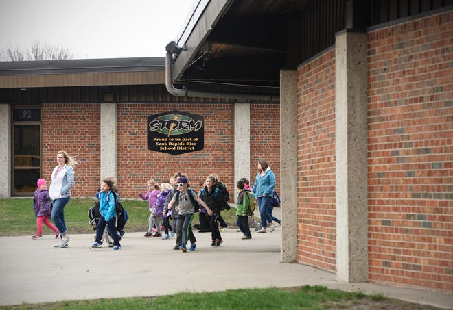 Students walk out the front school doors to board buses for home in this photo from 2017 at Pleasantview Elementary School in Sauk Rapids.
