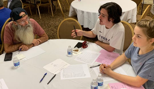 Perennial Vero Beach City Council candidate Brian Heady, left, listens intently to Ethan Hudson at a public meeting to discuss parking issues in the city's beachside shopping district Sept. 24, 2019, at the Holiday Inn Oceanside. Hudson's friend, Maggie McNabb, is at right.