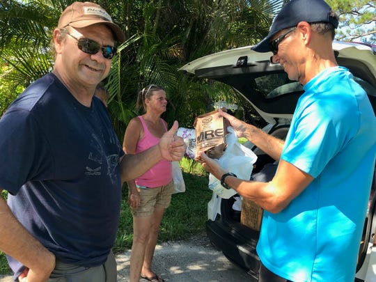 "Bjorn ""B.J."" Moene, right, hands Martin County resident Leo W. an MRE, or Meal Ready to Eat. Leo, who has been through rehab, recently was able to start renting a room. ""I use to avoid the homeless,"" said Moene. ""Then I became a Christian, and I was changed. The best gift ever is to help someone less fortunate and maybe help someone see the good in the world and start that person on the way to his or her recovery."""