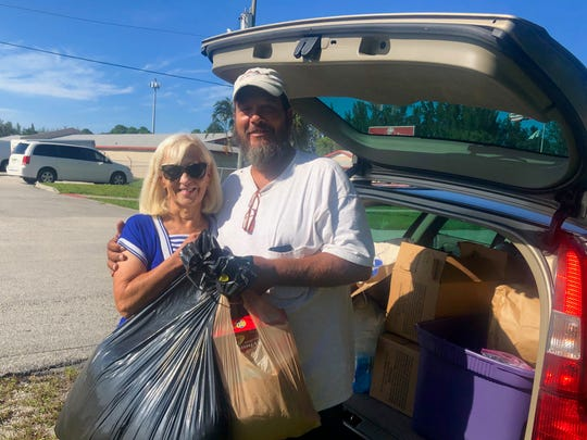 "Roberta Scott, left, gives supplies to Jeff ""Tex"" B., a homeless man in Martin County. ""Each person I have met touches my heart,"" Scott said. ""They're grateful for what we do, and I enjoy getting to know them."""