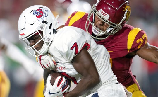 USC safety Brandon Perdue, right, tackles Fresno State wide receiver Derrion Grim during a game on Aug. 31. Because of injuries, Perdue, a Simi Valley native, is penciled in as the backup quarterback for the Trojans.