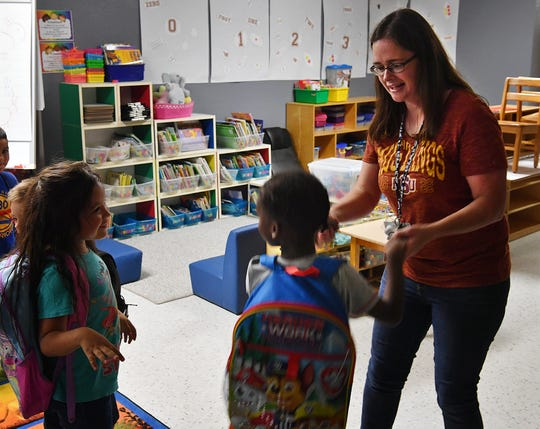 Students dance with their kindergarten teach, Stephanie Roberts, at the end of class at Lamar Elementary.