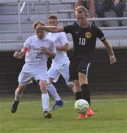 Tri-Valley's Mason Dunn hits a pass against Maysville's Joe Morrison in a match from last season. Dunn is headed to Ohio Dominican to continue his soccer career.