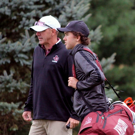 John Glenn coach Chad Orecchio, left, confers with his son, Bo, during a match last season at River Greens. Bo will play in his third district tournament on Monday at EagleSticks.