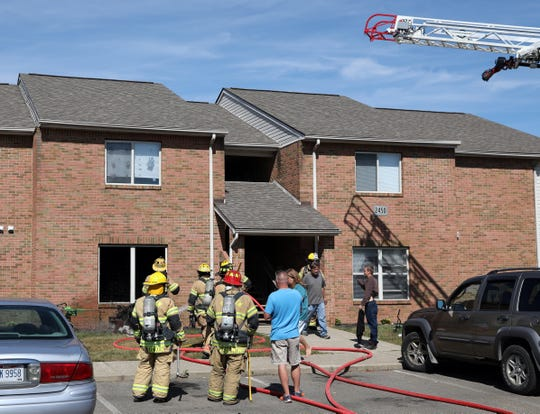 Firefighters gather outside 2450 Vista View Drive in Nashport after fire damaged an apartment and sent an elderly woman to the hospital.