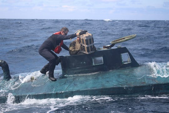 Coast Guard boarding team members climb aboard a suspected smuggling sub in September.