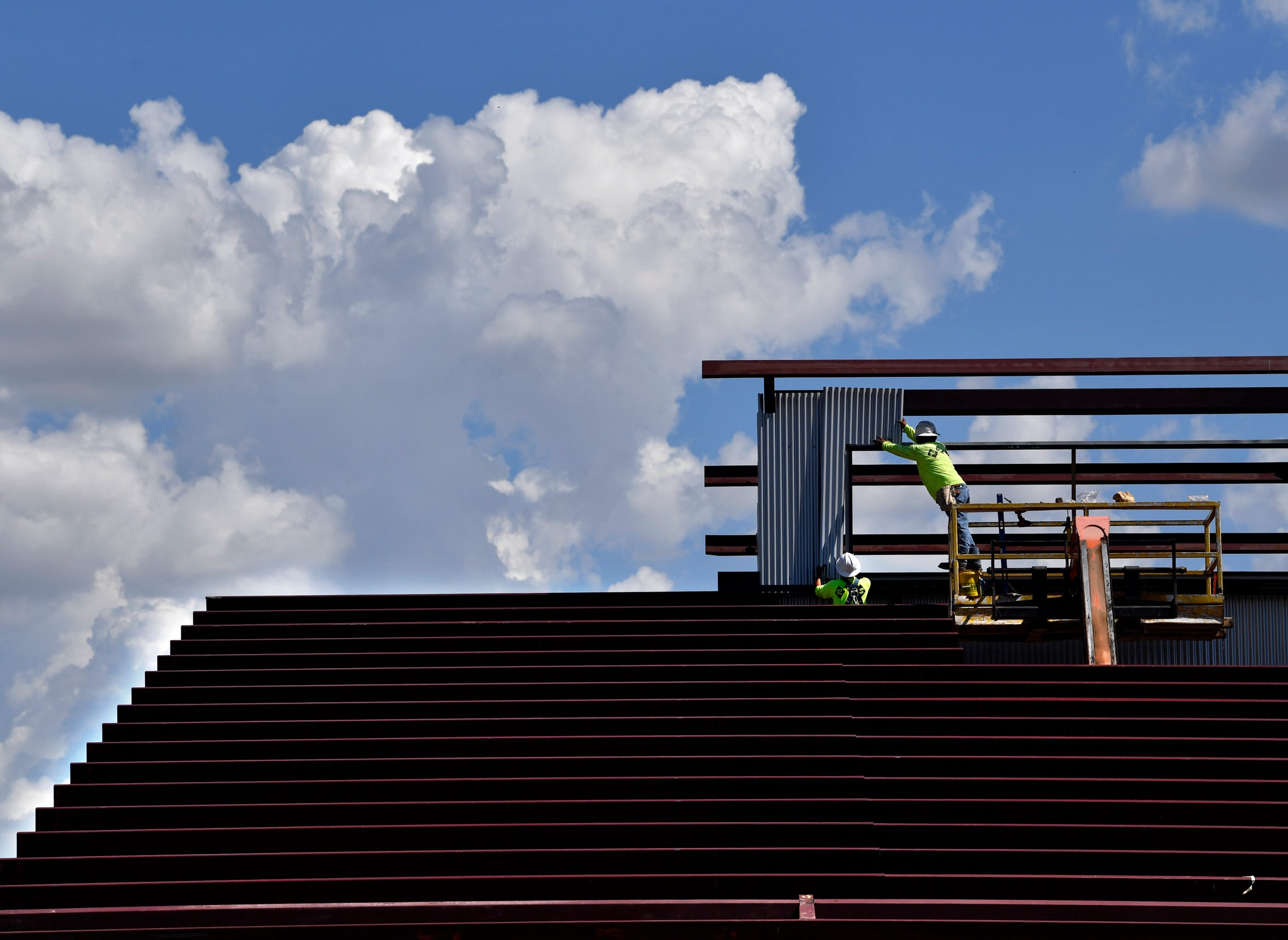 Workers install corrugated metal onto the frame of the new Sockdolager Brewing Co. on Sept. 26. The new location of the brew pub is on South First Street, where the Matera Paper Company stood before burning to the ground in 2012.