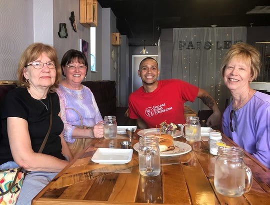 Village Food Tours founder Halim Urban, in red, and guests enjoy a tour stop at Paisley Vegan Kitchen in Cocoa Village.