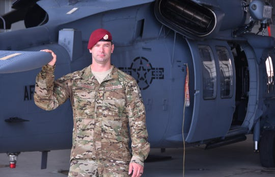 Air Force Tech. Sgt. Nick Torres stands alongside an HH-60G Pave Hawk helicopter at Patrick Air Force Base.
