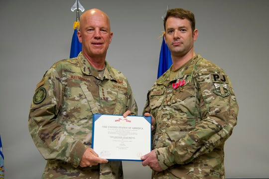 "Air Force Gen. John W. ""Jay"" Raymond (left), who commands the U.S. Space Command, presents two Bronze Star medals to Tech. Sgt. Nick Torres in June at Patrick Air Force Base."